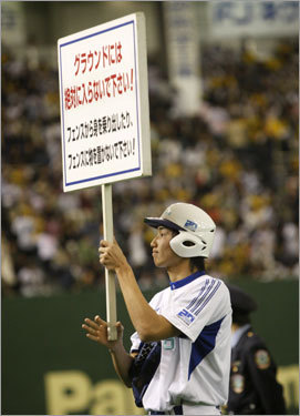 A Tokyo Dome employee held a sign warning fans not to go on the field. On the other side of the sign it warns fans to be wary of foul balls.