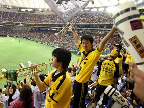 In Japanese baseball, the loudest cheering sections are near where American bleacher seats are located. Here fans of the Hanshin Tigers led their fellow fans in loud organized chants with much flag waving and music playing.