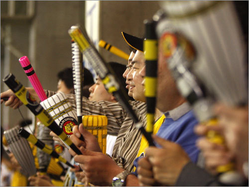 Hanshin Tiger fans beat noise making plastic sticks together in unison.