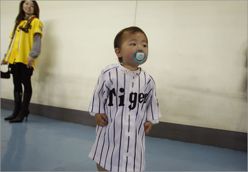 A young Hanshin Tigers fan sports a jersey.