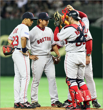 Daisuke Matsuzaka (No. 18) talks to his Red Sox teammates on the mound in the second inning.