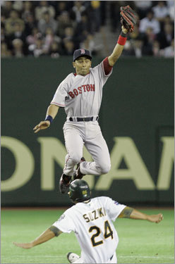 Red Sox shortstop Julio Lugo jumps to catch the ball as Athletics catcher Kurt Suzuki steals second in the second inning.