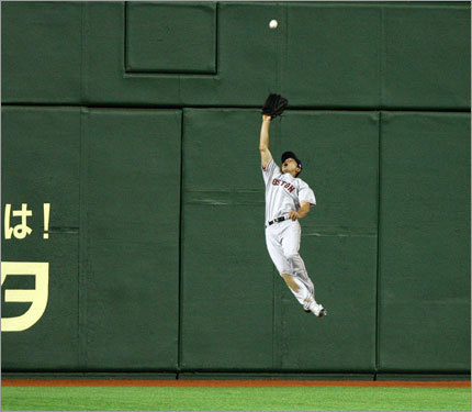 Red Sox center fielder Jacoby Ellsbury (center) jumps to catch the ball hit by Oakland Athletics' Emil Brown (not pictured) in the eighth inning.