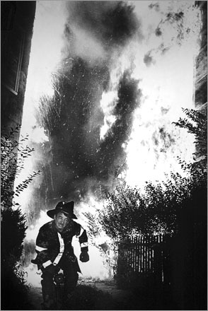 A Boston firefighter runs from intense flames and falling debris as two triple decker homes burn on Sydney Street in Dorchester in 1982.