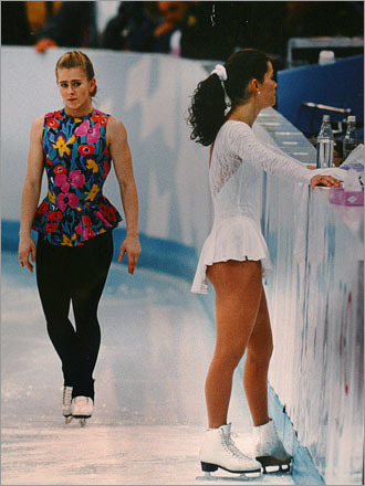 Tonya Harding (left) gives the eye to Nancy Kerrigan as Kerrigan talks with her coach duriing practice for the ladies' ice skating competition for the 1994 Winter Olympics in Norway. Kerrigan is practicing in the same brilliant white outfit she wore in Detroit the Friday afternoon she was attacked by a hit man hired by Harding's entourage.