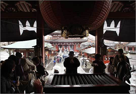 Visitors to the Sensoji Temple in Asakusa, Japan stopped to pray at the entrance of the Main Hall before entering.