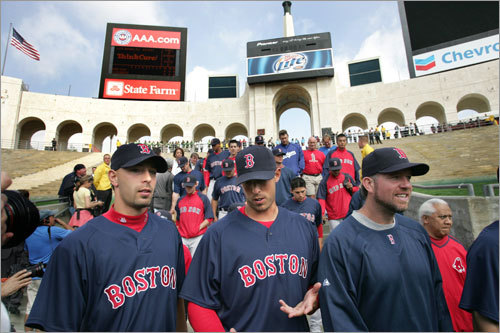 Red Sox players (from left) David Aardsma, Lincoln Holdzkom, Sean Casey walk onto field at the Los Angeles Coliseum before the start of an exhibition baseball game against the Los Angeles Dodgers on Saturday.