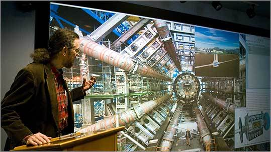 Tufts physicist Austin Napier uses the university's new 'VisWall' to show the workings of high-energy particle research at Europe-s CERN particle collider.