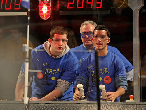 From left, Alban Cobi and Bruno Piazzarolo of John D. O'Bryant School of Math & Science operated under the watchful eye of coach Mike Sullivan. The students were competing at the Boston FIRST Regional Competition, a contest for high school robotic teams.