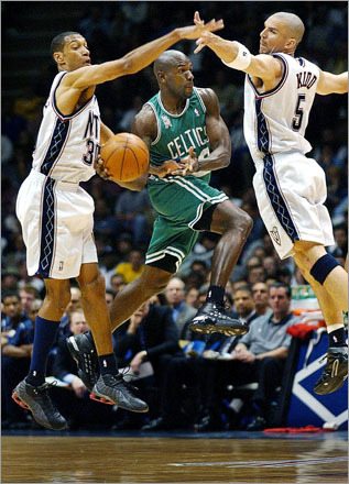 Buy photographs by Jim Davis Celtics guard Tony Delk splits the Nets' Kerry Kittles (left) and Jason Kidd as he throws a pass in 2002.