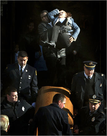 Overwhelmed by grief, Lydia Gomez, aunt of drowning victim Victor Baez, is carried from church after an emotional funeral Mass for four young boys who plunged through thin ice on the Merrimack River in Lawrence, MA.