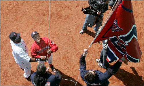Boston Red Sox legend Johnny Pesky, second from left, gets a hand from David Ortiz while raising the championship banner.