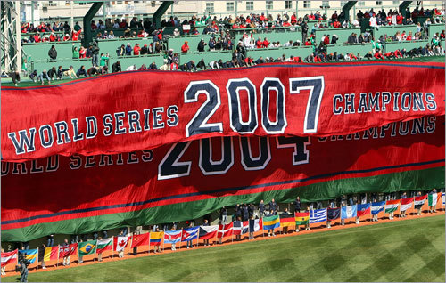 The 2007 World Series Champions banner is unfurled over the 2004 banner on the Green Monster.