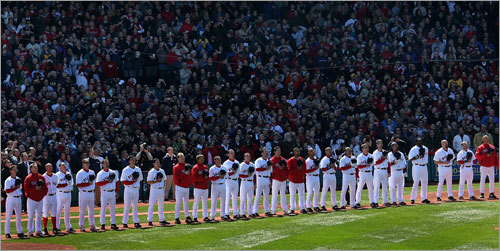 Member of the Red Sox stand on the first-base line for the national anthem.