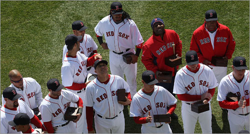 Members of the Red Sox watch the 2007 World Series championship banner get raised in center field.
