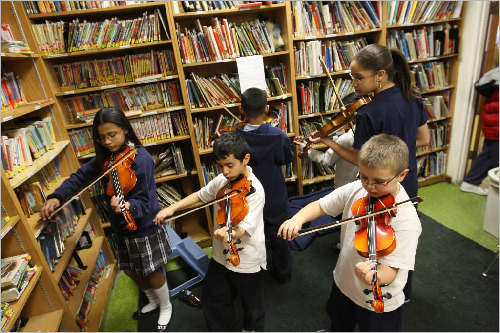 Led by Audris Terrero, 14, (right), students at the Community Day Charter School in Lawrence practiced in the library on their violins, as part of an after-school program for inner-city youth known as Lawrence Strings. The program is run by The North Shore Youth Symphony Orchestra.