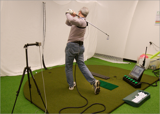 GolfTEC in Burlington, MA offers technology based critiques and improvements in the golf strokes of its clients. Client Mark Woods takes a practice swing in one of the bays outfitted with Sevapro technology and software.