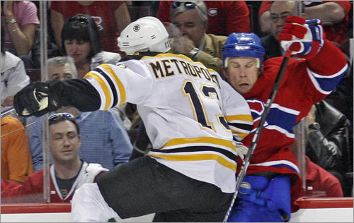 Boston's Glen Mertopolit, left, checks Montreal's Mike Komisarek into the boards.