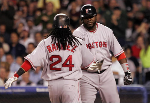 David Ortiz (34) greets teammate Manny Ramirez at home plate after Ramirez's second home run of the game in the third inning.