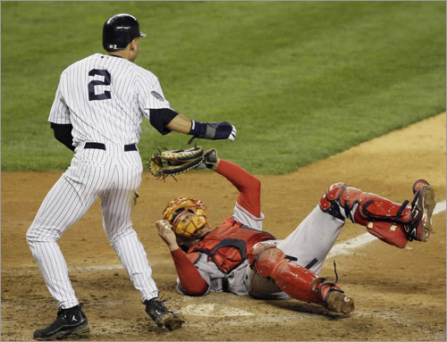 Derek Jeter (2) pops up off the plate after sliding home safely ahead of the tag from Red Sox catcher Jason Varitek on a double by Bobby Abreu during the fifth inning.