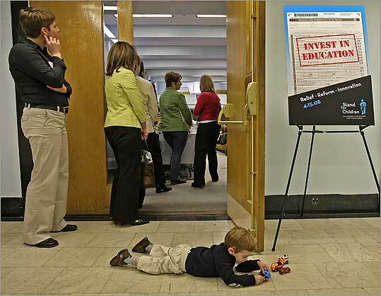 Bennett Cavillo, 2, played at the entrance of Gardner Auditorium while his mother, Nicole Abair of Lexington, waited in the doorway. Abair was among hundreds of parents and education advocates who turned out for Stand for Children's lobbying day at the State House to oppose severe cuts in education spending.