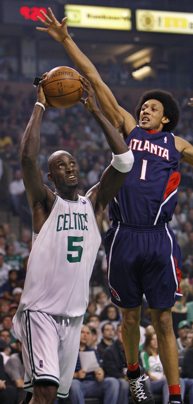 Kevin Garnett (5) goes under Atlanta's Josh Childress during first-half action.
