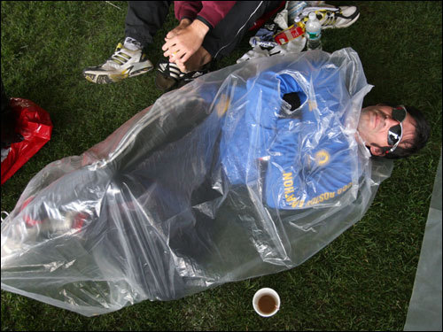 Jose Maora of Argentina tried to stay warm in a plastic bag at the Athletes Village at Hopkinton High School.