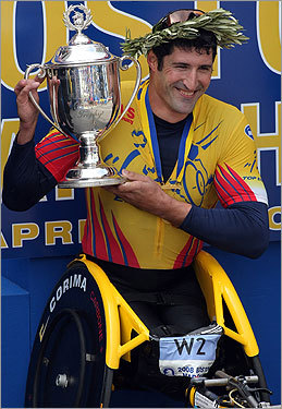 Wheelchair first-place winner Ernst Van Dyk held his trophy after crossing the finish line.