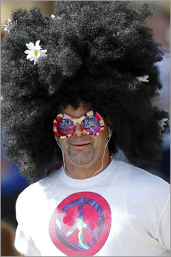 A runner wore a wig and sunglasses while he climbed a hill near the 1 mile marker in Hopkinton.