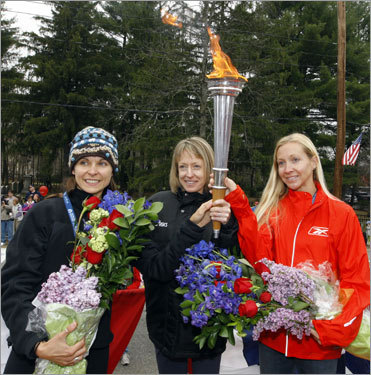 The top three finishers in the US women's Olympic Marathon Trials in Boston, Magdalena Lewy-Boulet (left), Deena Kastor (center), and Blake Russell (right), posed with a torch near the start line of the 112th Boston Marathon. Lewy-Boulet, Kastor, and Russell will represent the United States in the 2008 Beijing Olympics.
