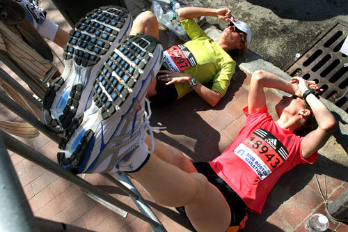 Runners Julie Arko (left) from St. Louis Park, Minn. and her friend Jackie Ghylin (right) from Lakeville, Minn. propped their legs up on a security barrier in the finish area on Boylston Street. Holding their legs up helped get their blood flowing back to normal.