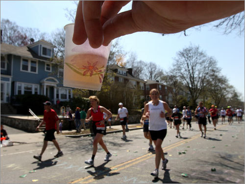The hand of Craig Jones of the Boston Hash House Harriers offered beer to runners on Heartbreak Hill.
