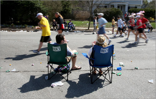 Sitting in comfort, Henry Timmons (left) and Katie Timmons (right) watched as back-of-the-pack runners climb Heartbreak Hill.