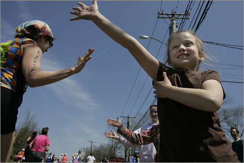Mary Grace Hanstad, 5, of Hollliston, had trouble holding up her arm during a day of giving support to the runners on Washington Street.