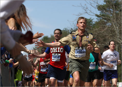 A runner dressed as a boyscout ran in front of Wellesley College during the 112th Boston Marathon.