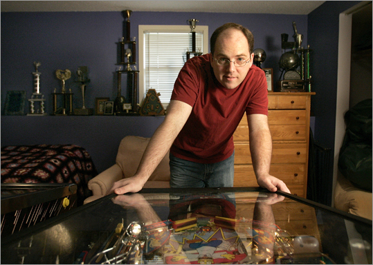 Bowen Kerins, the world flipper pinball champion, hunches over a Simpsons Pinball Party pinball game at his home in Salem.