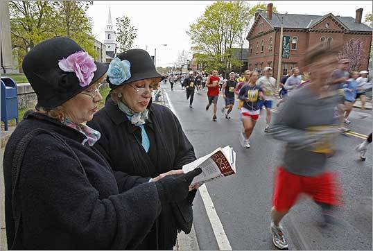 Jan DeBenedictis, left, and her twin sister, Lyn DeBenedictis, of Needham, read the poem, 'chamber Muxic,' from James Joyce's book, 'The Portable,' during the James Joyce Ramble 10 K in Dedham Square.