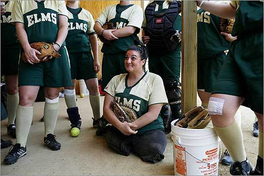 Gina Gilday, catcher on the Elms College softball team, listened to coach Cheryl Condon with her teammates before a game against Johnson State in Chicopee.