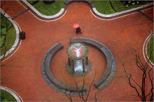 The park in Post Office Square was nearly deserted as a passerby walked by the fountain during a heavy downpour in the early afternoon. The photo was taken from a 22nd floor office building on Federal Street.