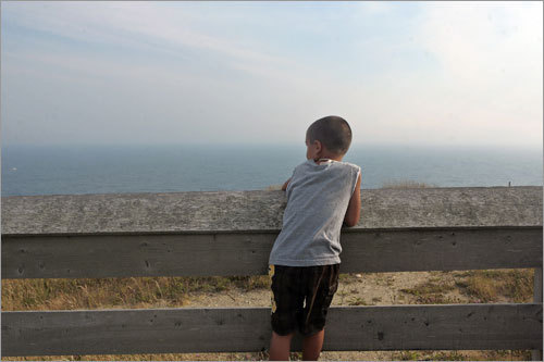 Alexander of Owego, N.Y., looks out over the Atlantic Ocean from atop the Mohegan Bluffs on Block Island.