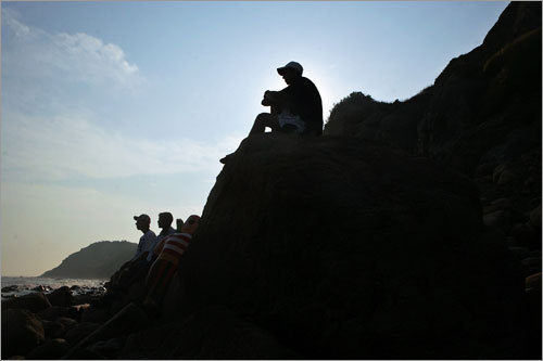 Jeff Rusack, Ashish Mohanty, and Alex Eller watch the waves from the rocky shore beneath the Mohegan Bluffs.