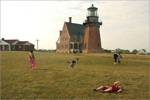 Ashley of Owego, N.Y. and her sons Anthony, center (doing cartwheel), and Joey (in red) play on the lawn in front of the Southeast Lighthouse, built in 1875.