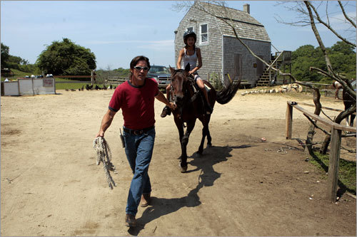 Timmy McCabe, owner of Rustic Rides Farms, leads Alexis, on horseback, to begin a trail ride through Rodman's Hollow to Black Rock Point.