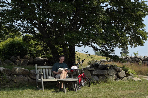 Richard Marsh of Roweyton, Conn., takes a break from his biking tour to read in the shade on Block Island.