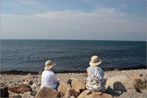 Kathy Ross, left, and her sister Margaret Grallert enjoy the view from shore near Sandy Point and the North Lighthouse. The two sisters have been coming to Block island since they were teenagers. 'It's remarkably unchanged,' Ross says.