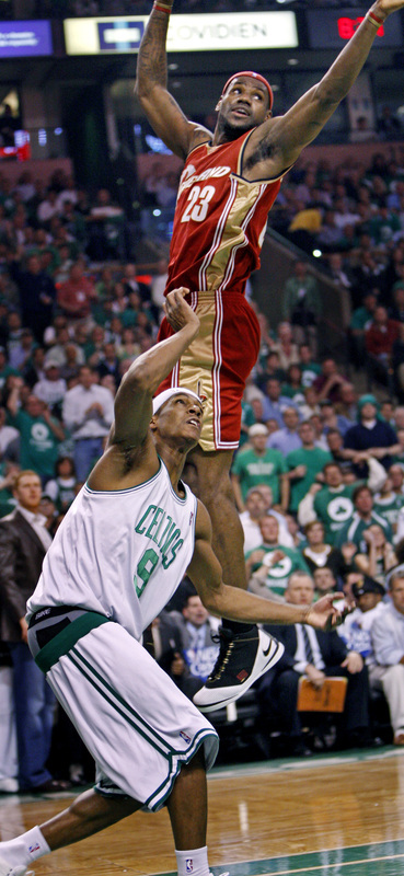 Cavaliers forward LeBron James sails by Celtics guard Rajon Rondo trying to block a layup attempt.