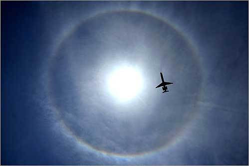 A jet approaching Logan International Airport was encircled by a halo around the sun. The ring and a faint rainbow in the upper atmosphere was caused by ice crystals within cirrus clouds.