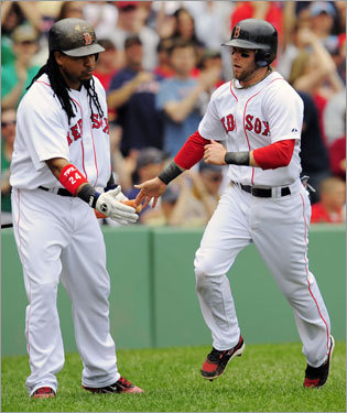 Dustin Pedroia (right) scored the first Red Sox run of the game on a David Ortiz double in the first inning. Manny Ramirez congratulated him after he scored.