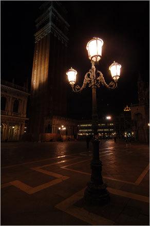 A lone street light illuminates Italian cobblestone streets.