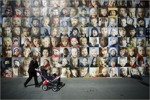 During the Reykjavík Arts Festival, a toddler gazes back at hundreds of portraits of children from rural Iceland, on display on a central street corner.